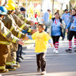 young child at the walk for kids receives high five at the walk for kids