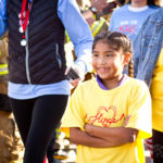 young girl crosses arms while smiling at the walk for kids 2018