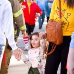young girl in butterfly shirt and butterfly sweatshirt high fives firefighter along side the UA mall walkway at the walk for kids 2018