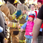 firefighter stand alongside the walk for kids walkway giving a high five to young girl in pink vest