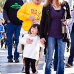 young girl wearing white sweater with pink cowgirl boots walks alongside smiling mother at walk for kids 2018