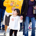 young girl wearing white sweater with pink cowgirl boots looks to the side while joining smiling mother at walk for kids 2018