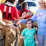 walk for kids 2018 photo with young girl with painted face smiling at firefighters alongside the UA mall walkway.