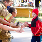 Walk for kids 2018 photo with young boy high fiving firefighter