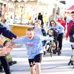 young boy excitedly runs to recieve high fives from passerbys at the walk for kids