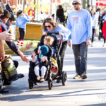 woman pushing two young children in double stroller and they give high fives to people standing on the sidelines