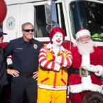 ronald mcdonald and santa pose for a photo with police officers infront of firetruck