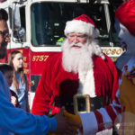 santa smiling and waving infront of firetruck while walking in the walk for kids