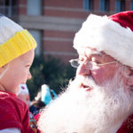 young girl smiles and looks at santa as he holds her smiling