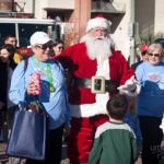 santa and two guests pose for photo at the walk for kids