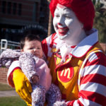 ronald mcdonald holding young child at the walk for kids