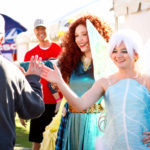 Tinkerbell and Merida cosplay princesses high five guests at the walk for kids