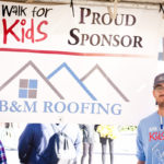 proud member of roofing company stands next to company banner for a photo at the walk for kids
