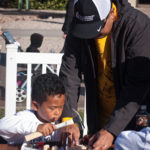 father and son work together to complete a craft at the walk for kids