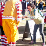 young girl gives ronald mcdonald a high five at the walk for kids