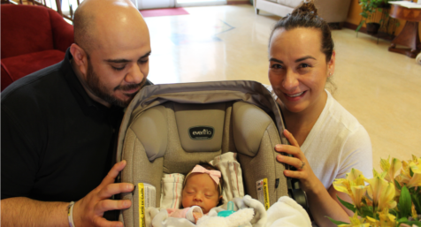Newborn Carpena sits in her carseat while her parents are smiling towards camera