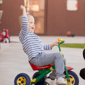 young boy mason holds fist in air while riding triciycle in the backyard of the RMHC