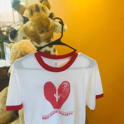 White shirt with red ringer and Red Shoe Society logo, hung on a stuffed giraffe