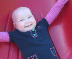 smiling child goes down on the red slide