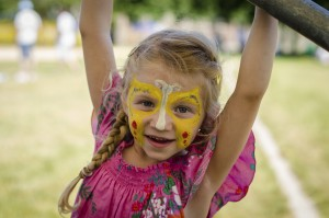 young girl is with yellow butterfly face paint is playing outside